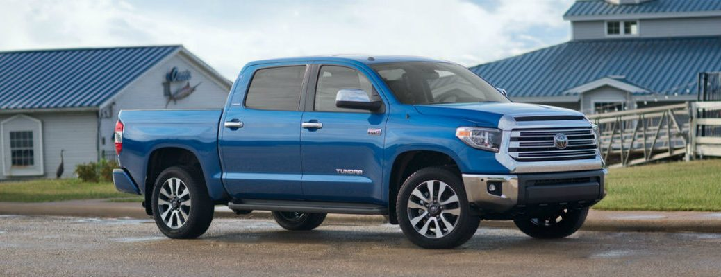 Profile shot of blue 2018 Toyota Tundra pickup parked on farm with farmhouse in background
