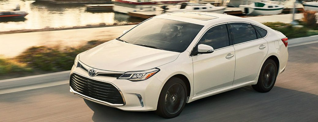 White 2018 Toyota Avalon driving down lakefront road with boats in view
