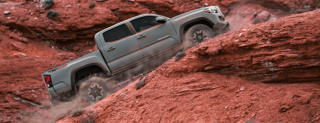Long shot of silver Toyota Tacoma scaling up desert hill