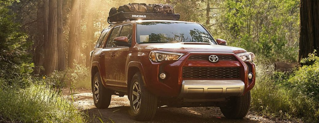 Front shot of red 2018 Toyota 4Runner parked on dirt trail in between two trees