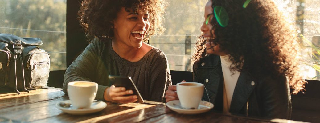 Two women smiling and laughing in a coffee shop