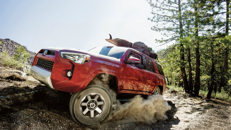 Red 2018 Toyota 4Runner driving up the side of a cliff