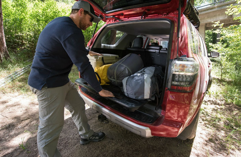 Back hatch of the 2018 4Runner with a man putting items inside