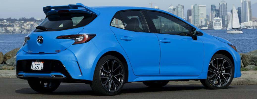 Profile view of blue 2019 Toyota Corolla Hatchback parked in front of city skyline
