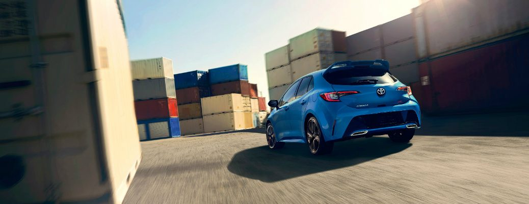 Blue 2019 Toyota Corolla Hatchback driving next to shipping crates