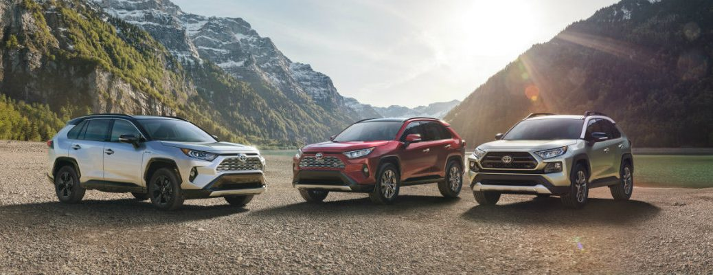 Three RAV4s with mountains in the background