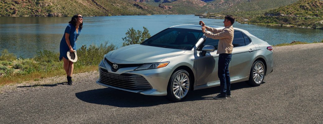 Two people standing on either side of silver 2019 Toyota Camry hybrid