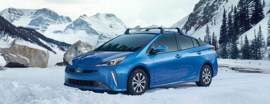 Blue 2019 Toyota Prius AWD-e trim parked next to snowy mountain road