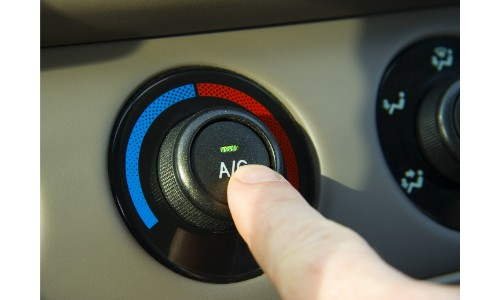 Hand pressing the A/C button of a car