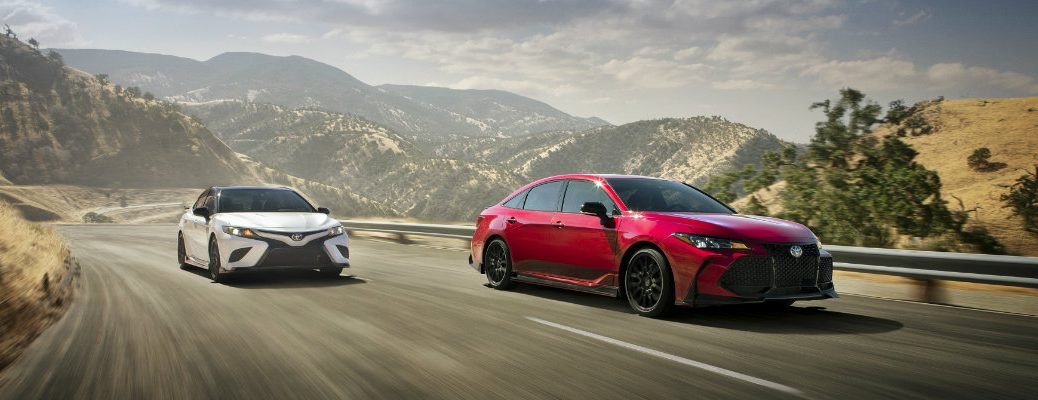 2020 Toyota Camry TRD driving past a 2020 Toyota Avalon