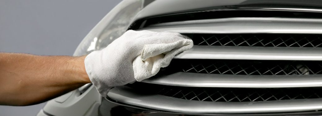Hand wiping down a chrome grille with polish