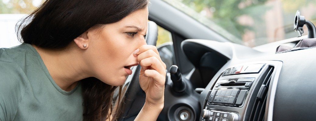woman covering her nose in her car
