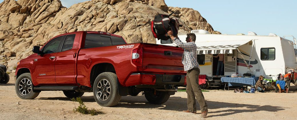 Red 2016 Toyota Tundra with Camping Gear and Camping Trailer in Background
