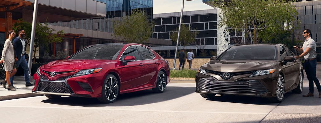 Ruby Flare Pearl And Brownstone 2018 Toyota Camry Models Parked By Office Buildings