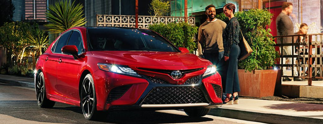 Red 2018 Toyota Camry With Black Roof Parked In Front Of Restaurant At Night