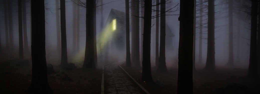Haunted house with a light on in dark woods