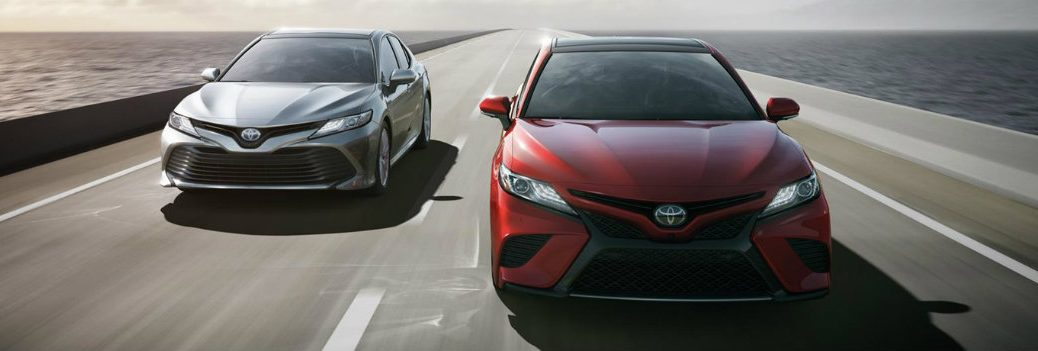 2018 Toyota Camry models driving down a highway over the sea