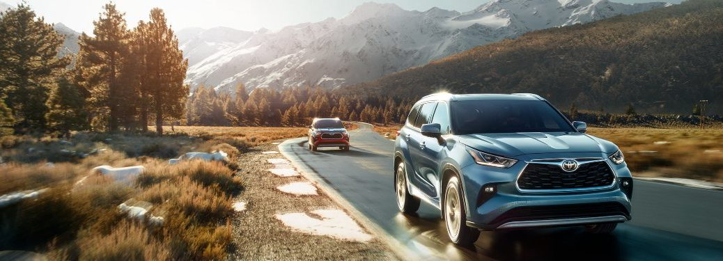 Two 2020 Toyota Highlander models driving down a highway