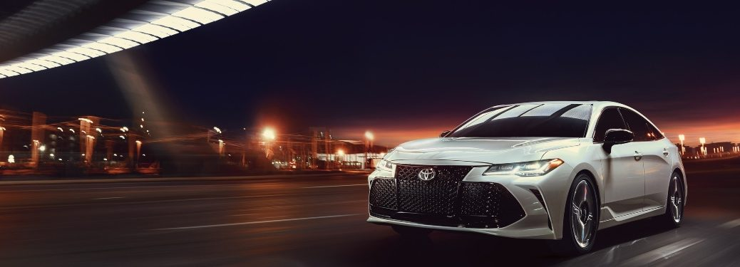 2020 Toyota Avalon driving down a city street at night