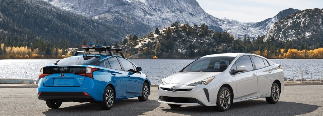 Two 2020 Toyota Prius models parked by a river