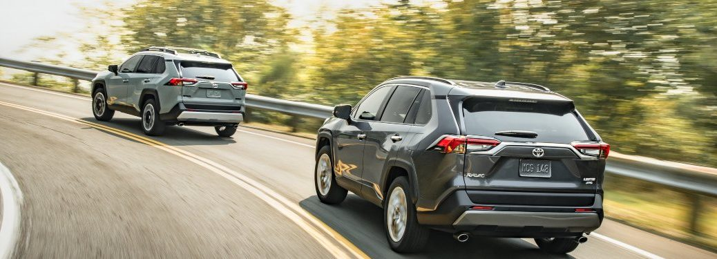 Two 2020 Toyota RAV4 models driving down a curving road