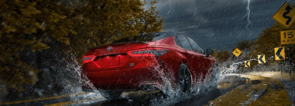 2021 Toyota Camry driving down a rural road in a storm.
