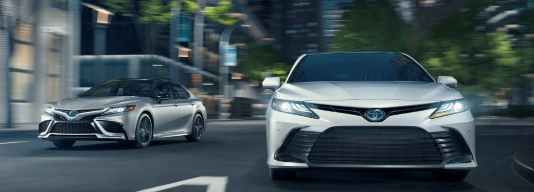 Two 2021 Toyota Camry models driving down a city street