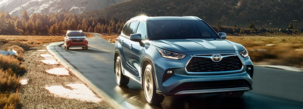 Two 2021 Toyota Highlander models driving down a rural road