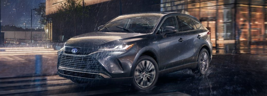 2021 Toyota Venza driving in front of a building in the rain