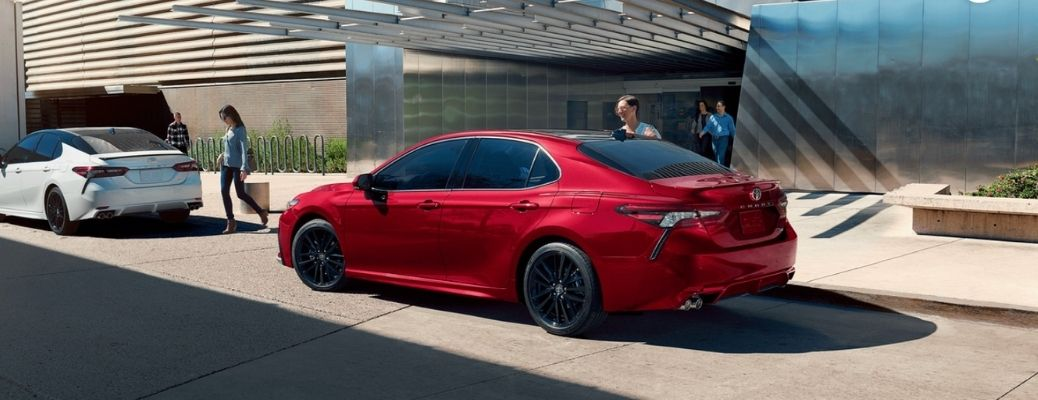 2021 Toyota Camry Hybrid Red on a parking spot. Read about the 2021 Toyota Camry Hybrid Performance