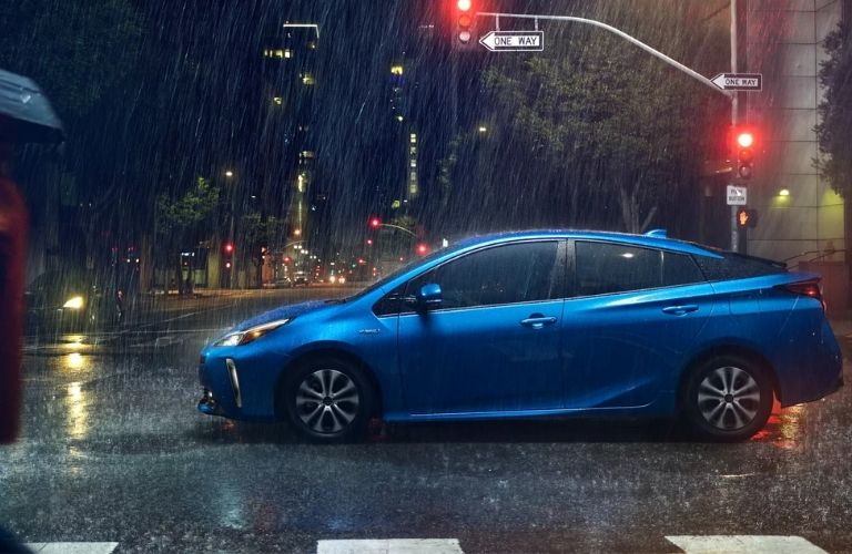 Side view of a blue 2022 Toyota Prius in the rain