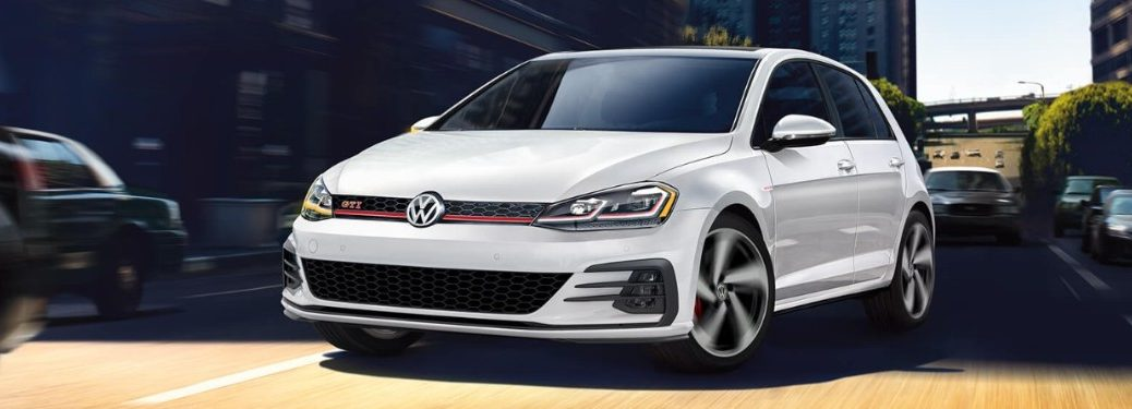 Front driver angle of a white 2019 Volkswagen Golf GTI driving down a road