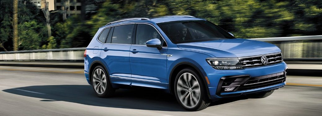Front passenger angle of a blue 2020 Volkswagen Tiguan driving down a road
