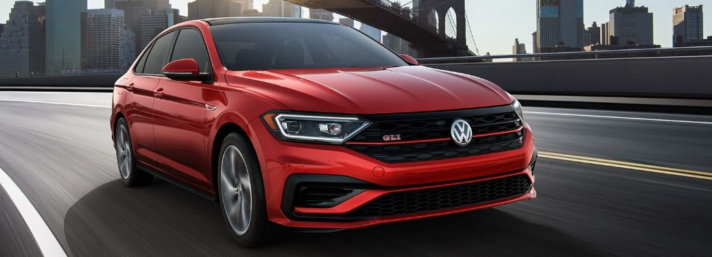 Front passenger angle of a red 2019 Volkswagen Jetta GLI driving on a bridge with a city in the background