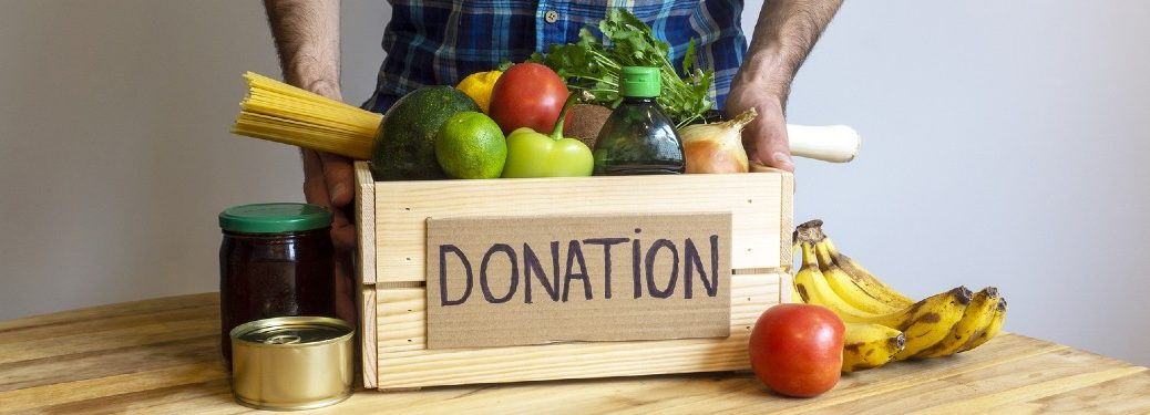 """Man standing behind a box filled with food and the word """"Donation"""" written on it"""