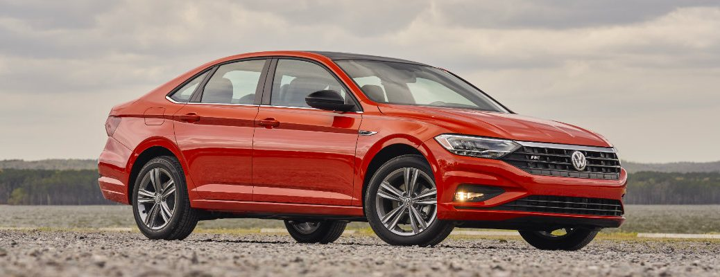 2019 Volkswagen Jetta R-Line trim level exterior shot parked on rocky ground with a forest and cloudy sky in the background