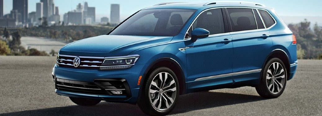 Front driver angle of a blue 2020 Volkswagen Tiguan with a city in the background