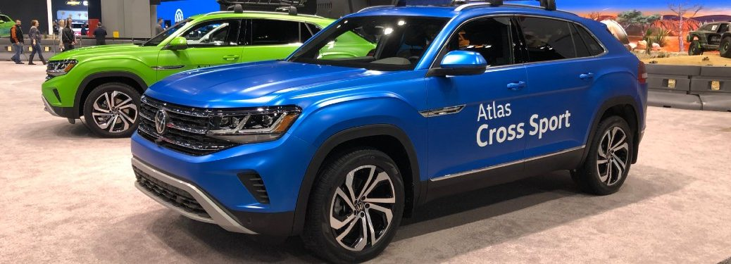 Front driver angle of a blue 2020 Volkswagen Atlas Cross Sport with a green 2020 VW Atlas Cross Sport behind it
