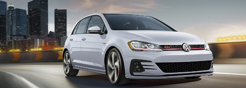 Front passenger angle of a white 2020 Volkwagen Golf GTI driving away from a city