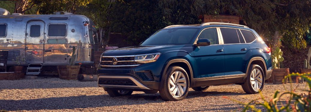 Front driver angle of a blue 2021 Volkswagen Atlas near a trailer