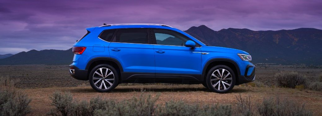 Passenger angle of a blue 2022 Volkswagen Taos with mountains in the background