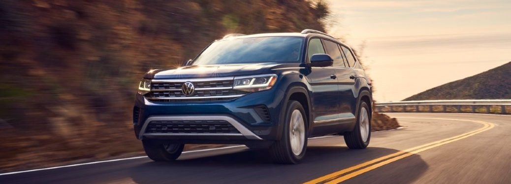 Front driver angle of a blue 2021 Volkswagen Atlas driving on a road