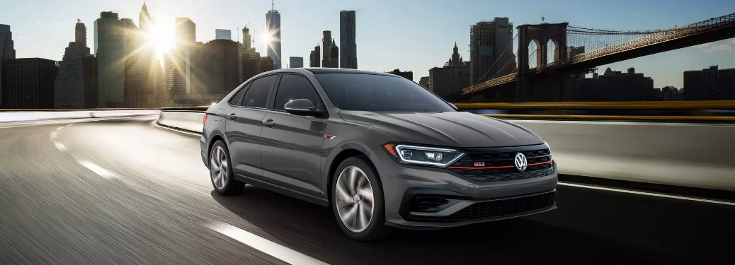 Front passenger angle of a grey 2021 Volkswagen Jetta GLI driving on a highway