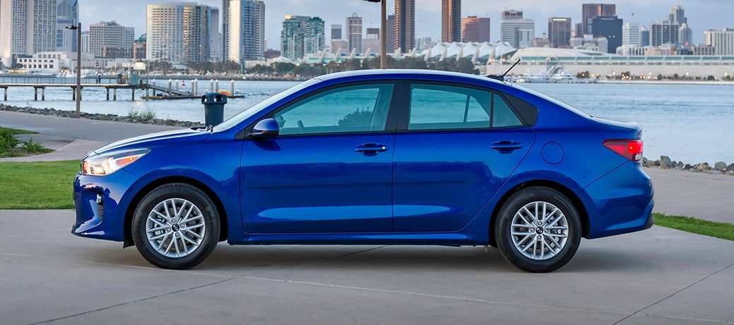 profile view of the 2018 kia rio in blue parked by a river in the city