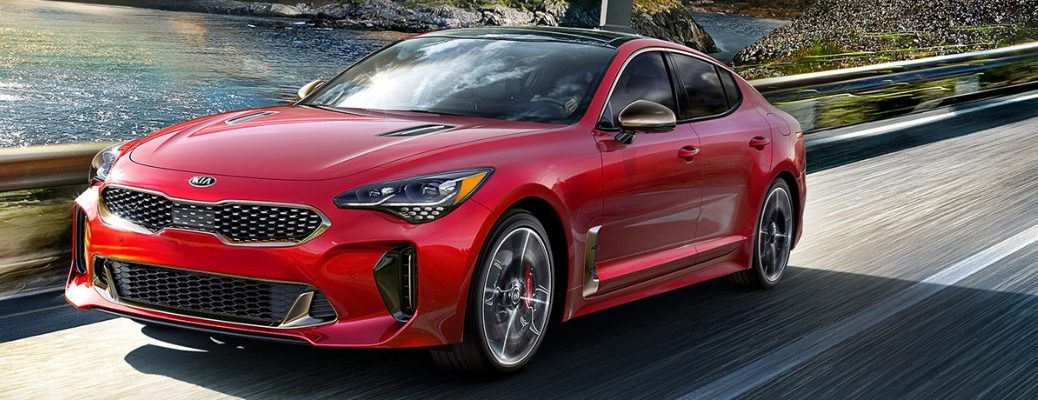 Red 2019 Kia Stinger driving on riverfront