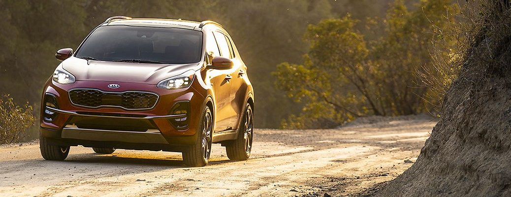 Front view of red 2020 Kia Sportage driving on empty country road
