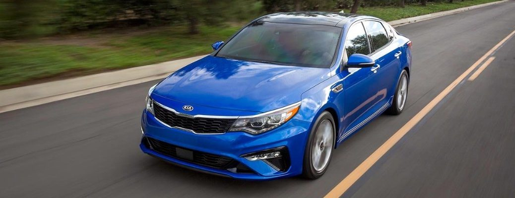 Blue 2019 Kia Optima driving on wooded road