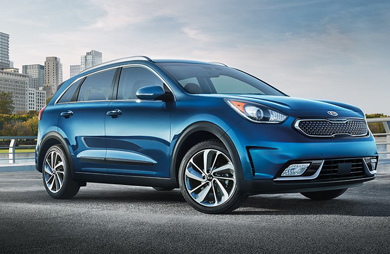 Blue 2019 Kia Niro driving with city skyline in background