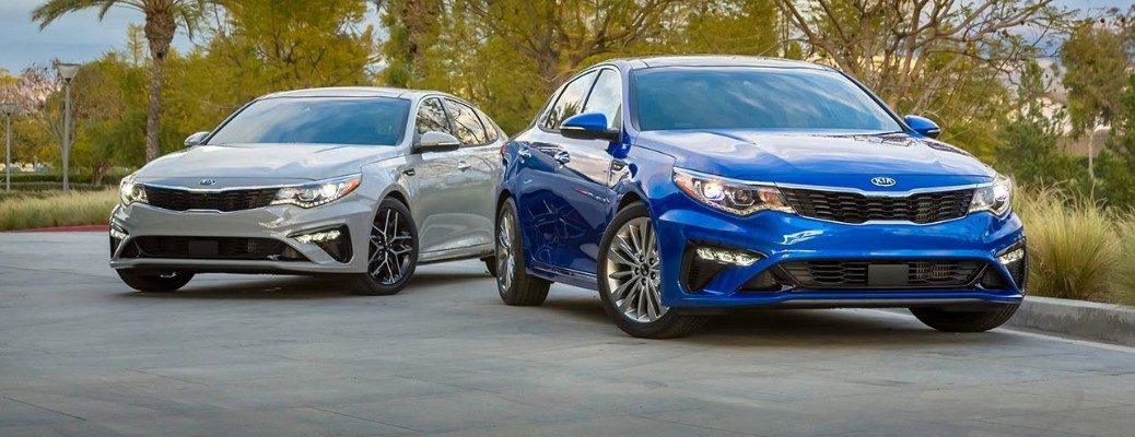 Two 2019 Kia Optima models parked in front of tree