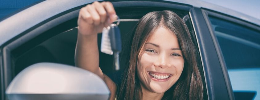 Image of a female teen driver showing off the keys to the new car she is sitting in